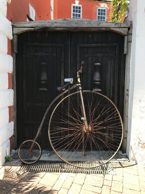 Old penny farthing parked on street pavement in sunlight