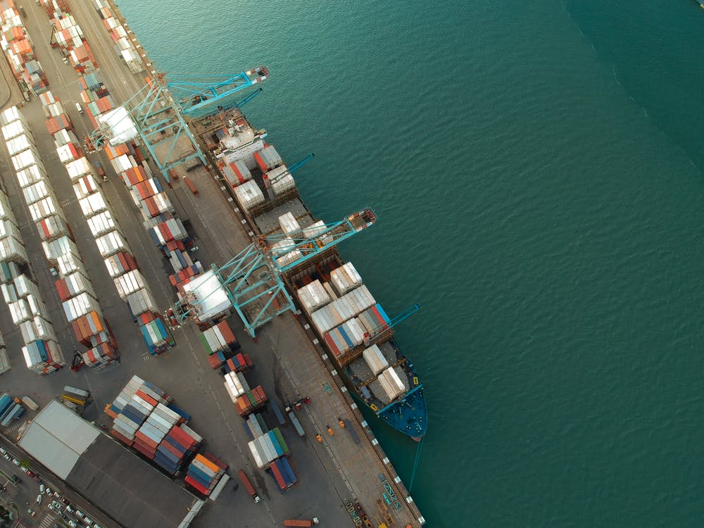 Top view of harbor with containers and cargo ships located near calm rippling sea water