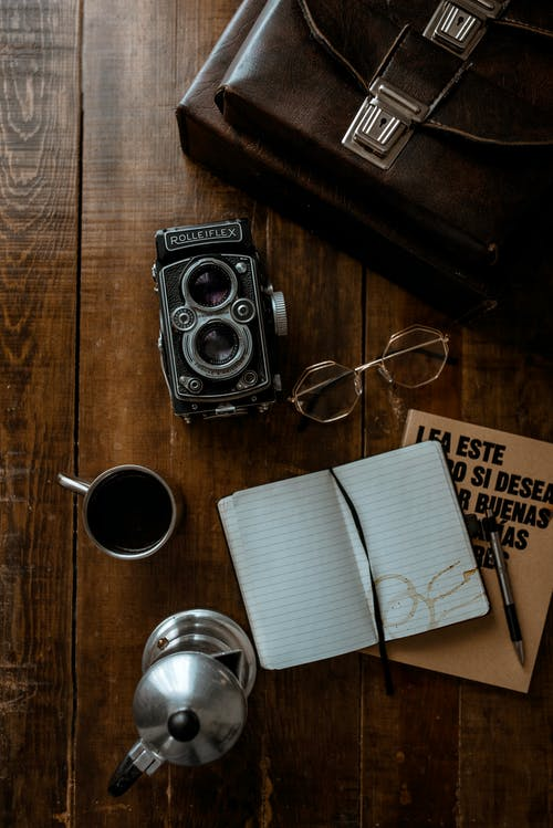 Black Camera Beside White Ceramic Mug on Brown Wooden Table
