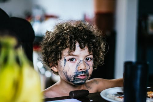 Boy with painted face standing near table