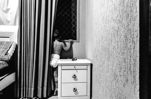 Black and white back view of anonymous boy in underwear standing in bedroom near curtains and looking through window
