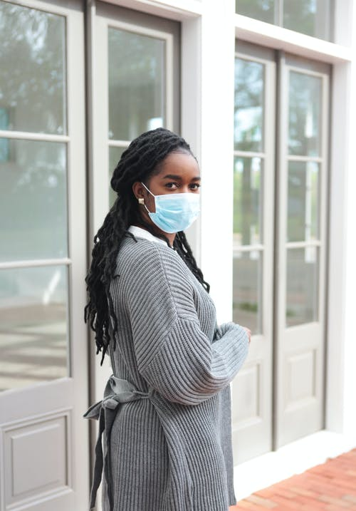 Woman in White and Black Stripe Long Sleeve Shirt Wearing Blue Face Mask