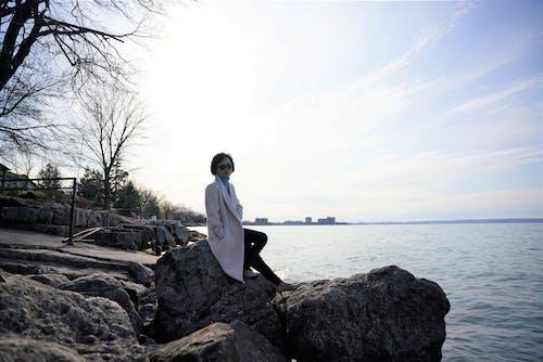 Young woman sitting on stony seashore on sunny autumn day