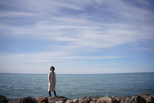 Young woman in stylish coat resting on stony seashore while standing with hands in pockets  near sea against sky with rare fluffy clouds in sunny autumn day