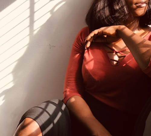 Crop calm African American female in smart casual sitting with legs crossed against white shabby wall and leaning on windowsill