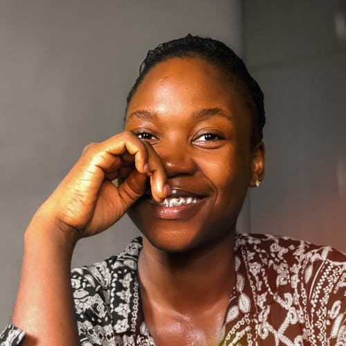 Portrait of positive African American female in casual wear touching face and looking at camera with toothy smile