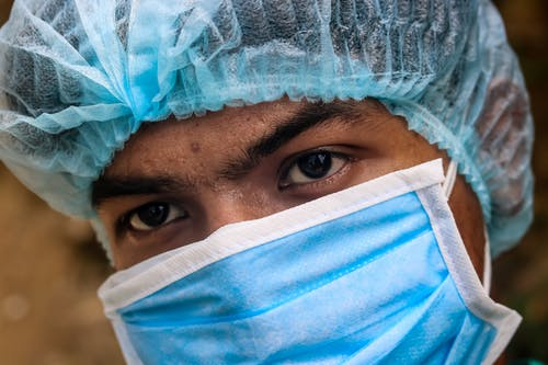 Crop ethnic male doctor in protective mask and hat