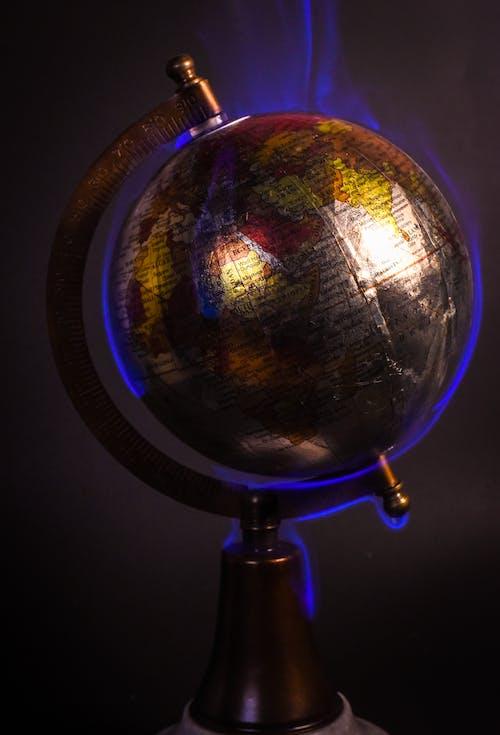 Earth globe burning in blue flames