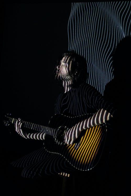 Guitarist performing music in neon lights in club