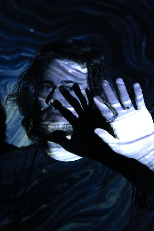 Unemotional man against bright neon light in dark room