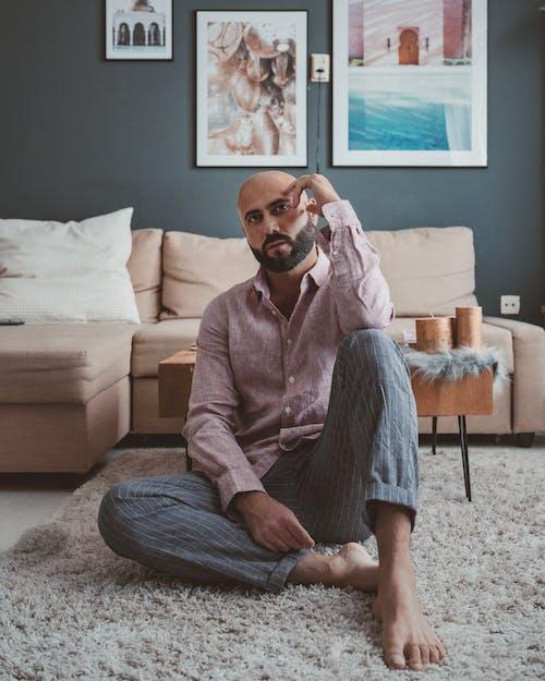 Bearded Man Sitting on a Gray Carpet