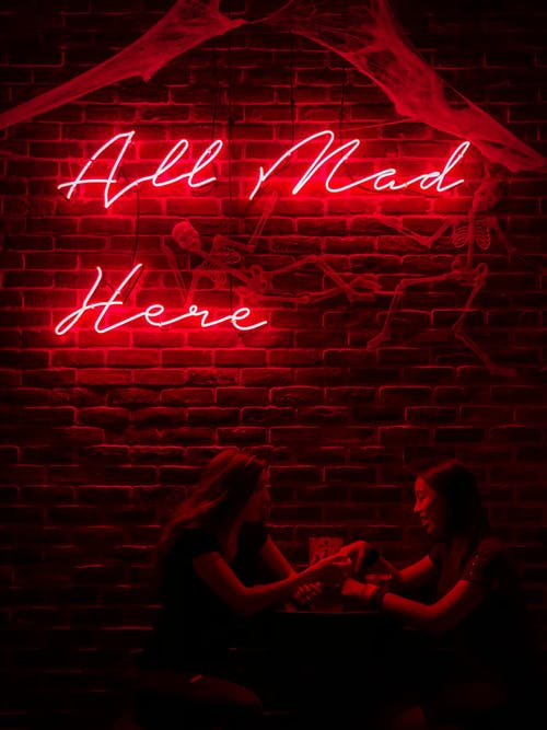 Women Sitting Under a Neon Sign