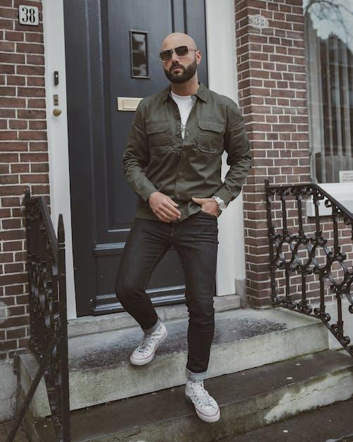 Serious bearded man on street doorsteps