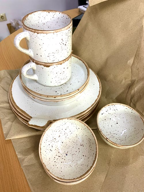 Set of white ceramic dishware on packing paper