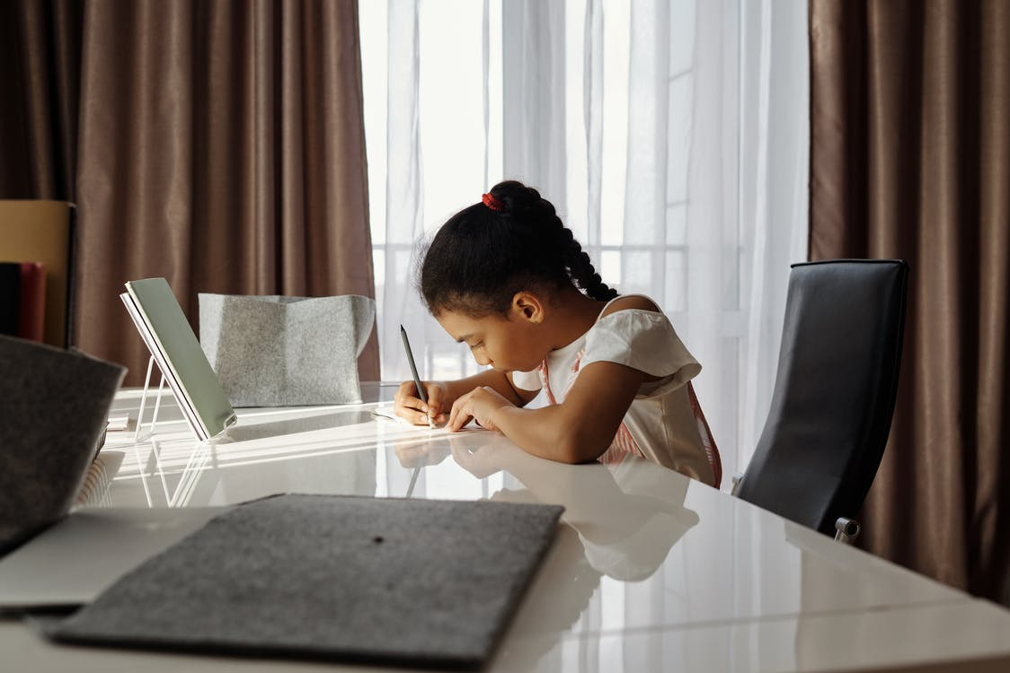 Little Girl Sitting at a Desk and Writing