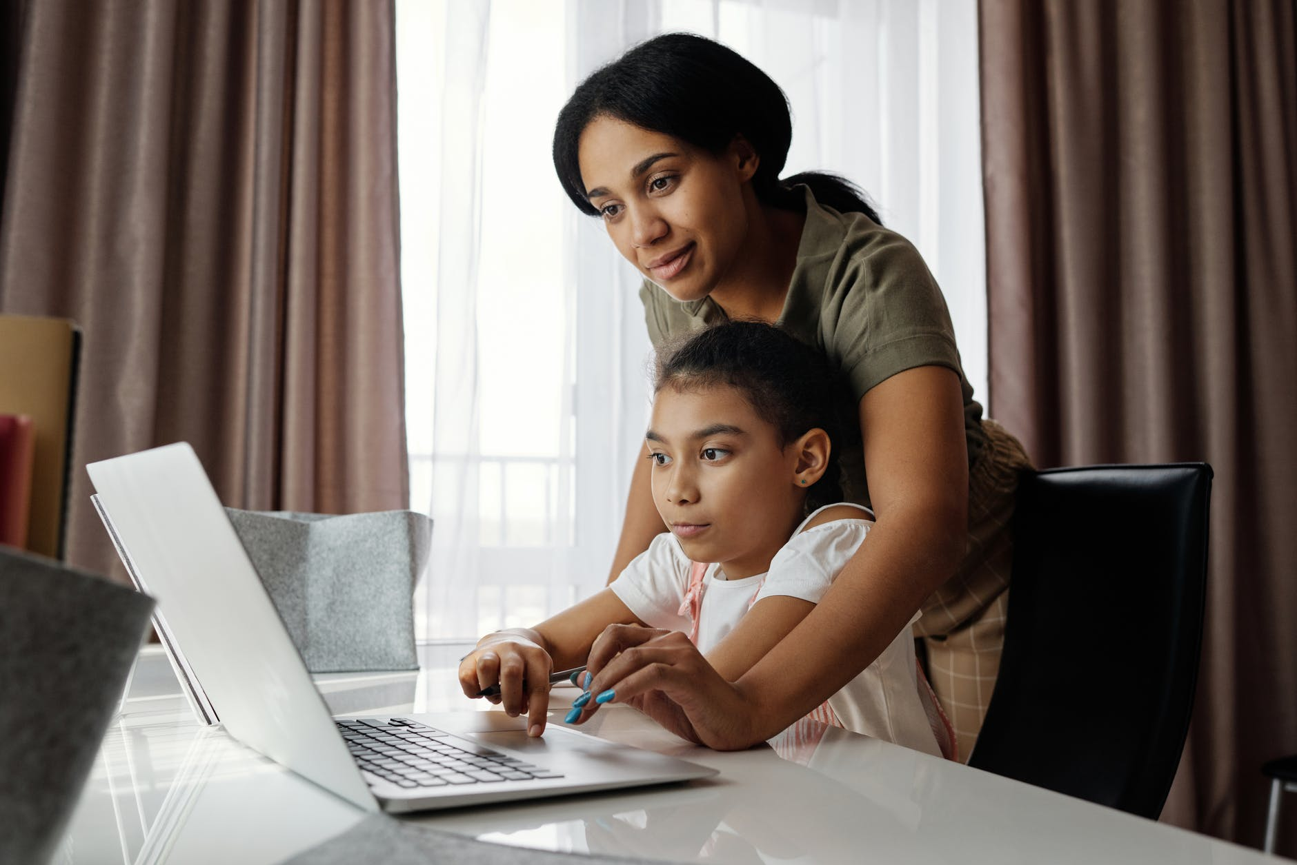 Mother helping her daughter to use a laptop