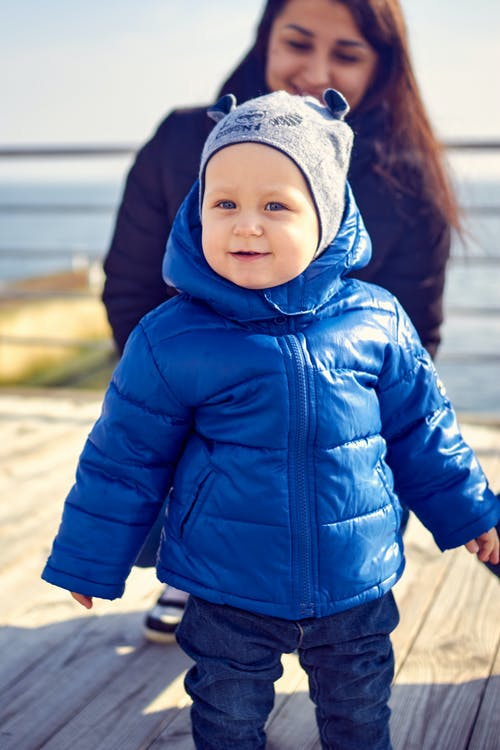 Close-Up Photo of a Cute Kid in a Blue Puffer Jacket