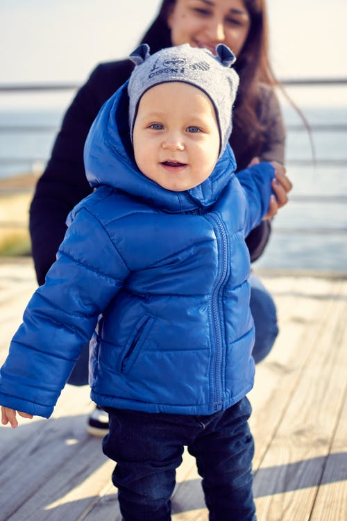 Selective Focus Photo of an Adorable Kid in a Blue Puffer Jacket