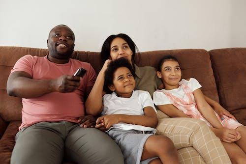 Família Sentada Em Um Sofá Marrom Assistindo Tv