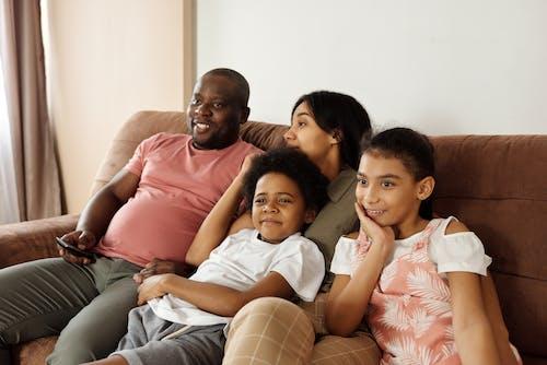 Família Feliz Sentada Em Um Sofá Assistindo Tv