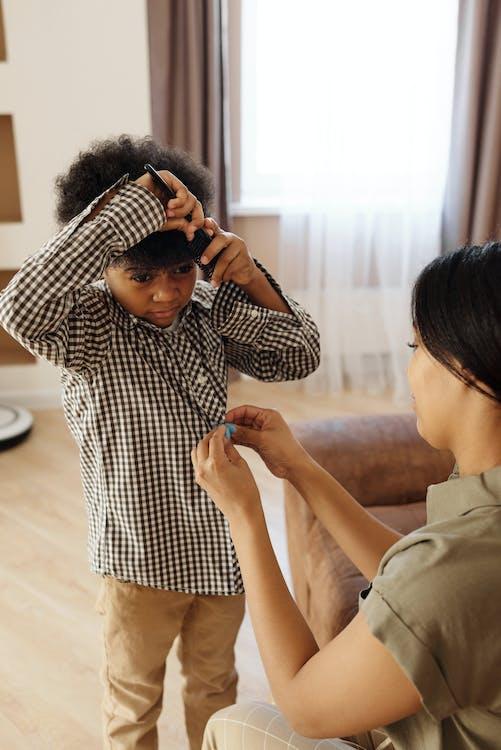 Madre Ayudando A Su Hijo A Cambiarse