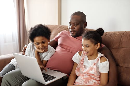 Father and Children Looking at a Laptop