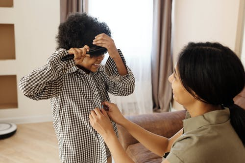 Ibu Mengancingkan Baju Pakaian Putranya