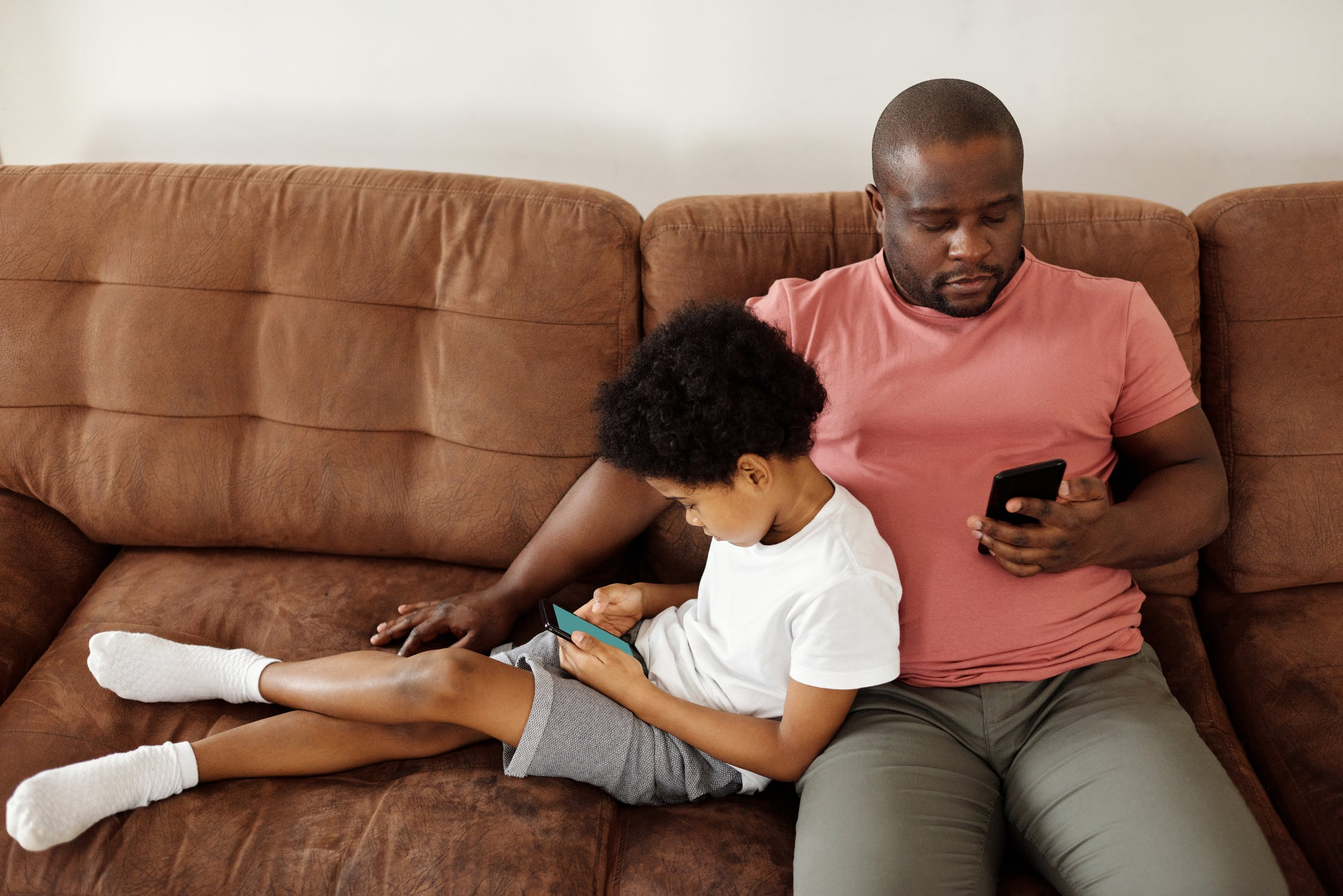 Father and son sit on the sofa looking at their phones. Photo by pexels user August de Richelieu. Photo used courtesy of pexels.com.