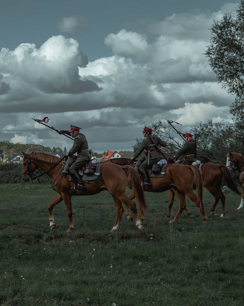 People Riding Horses on Green Grass Field Under White Clouds