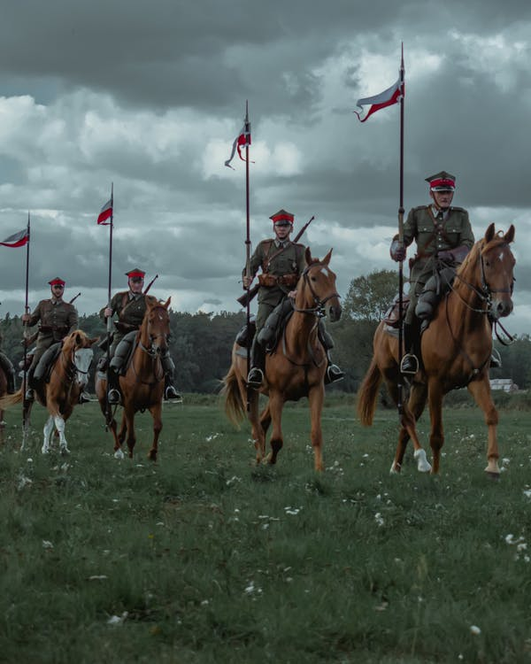 Men in Brown and Black Uniform Riding Horses on Green Grass Field