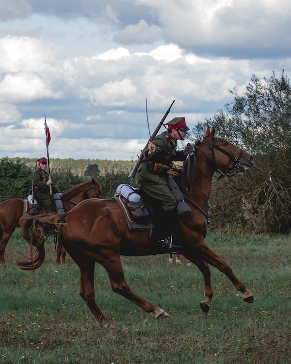 Man Riding Horse on Green Grass Field