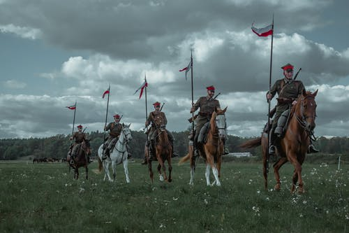 Soldiers in Brown and Black Uniform Riding Horses on Green Grass Field Under White Clouds during