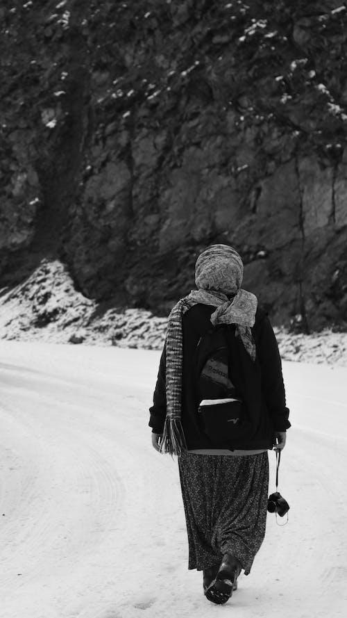 Unrecognizable woman strolling along snowy road