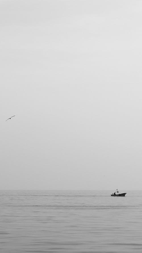Motorboat floating in waving sea against cloudy sky