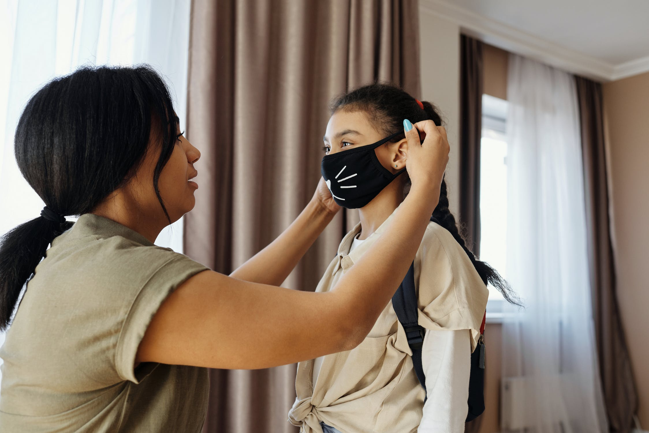A woman helps a young child put on a face mask. Photo by August de Richelieu. Used with permission from Pexels.com