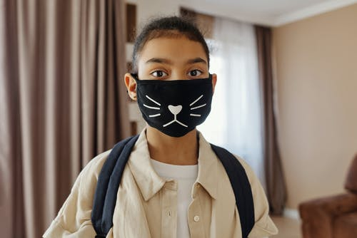 Little Girl Wearing a Face Mask With a Design