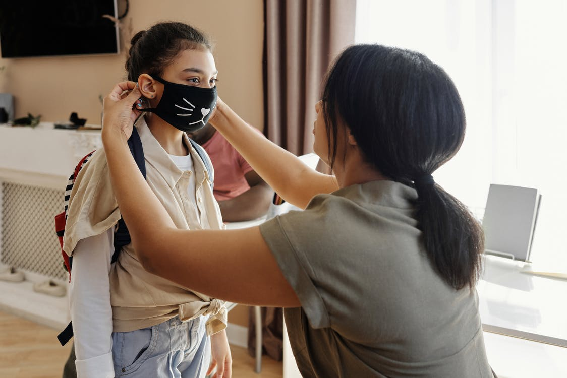 Mother Putting a Face Mask on her Daughter