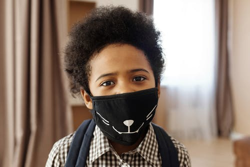 Little Boy Wearing a Face Mask With a Design