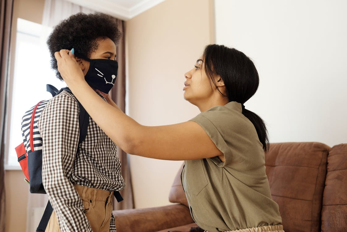 Mother Putting a Face Mask on her Son