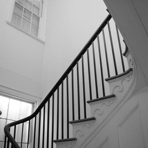 White Wooden Staircase With Black Metal Railings