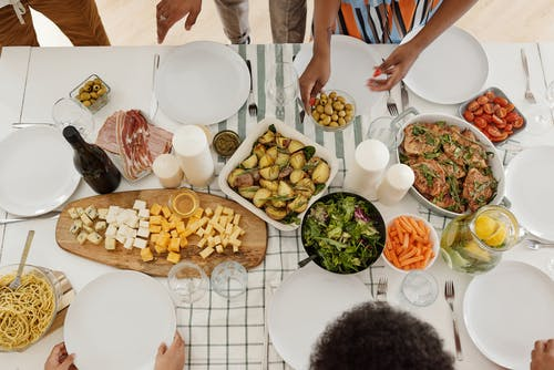 People Standing in Front of Table With Foods