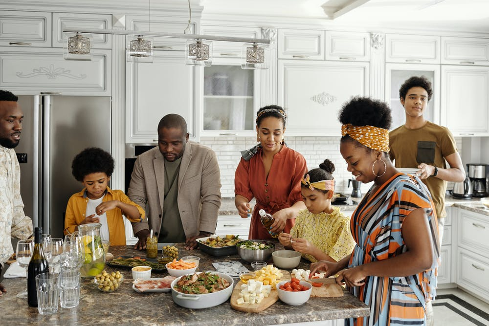 Family preparing food in the kitchen. | Photo: Pexels