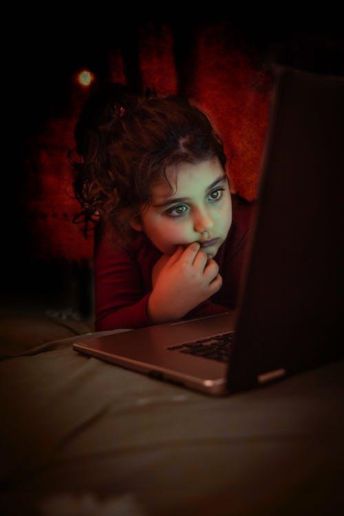 Pensive girl watching film on laptop