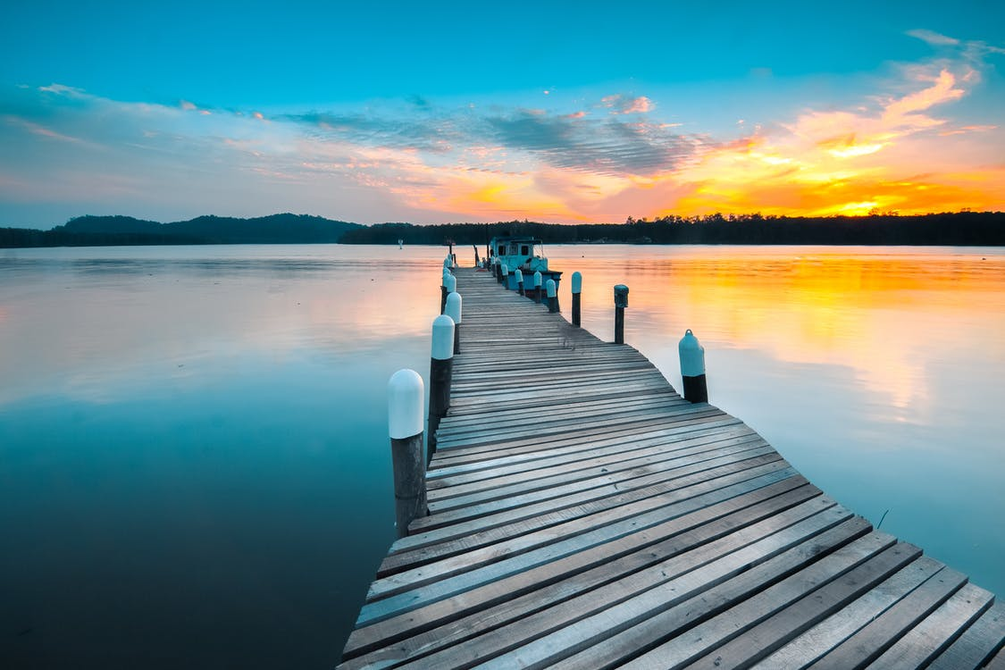Picturesque view of vivid sundown above forest and long wooden pier above calm reservoir