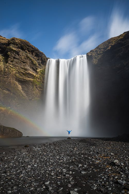 Unrecognizable traveler between rainbow and waterfall