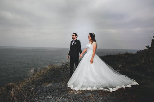 Full body of bride and groom in wedding suits holding hands and looking away with bright smile while walking on coast of sea