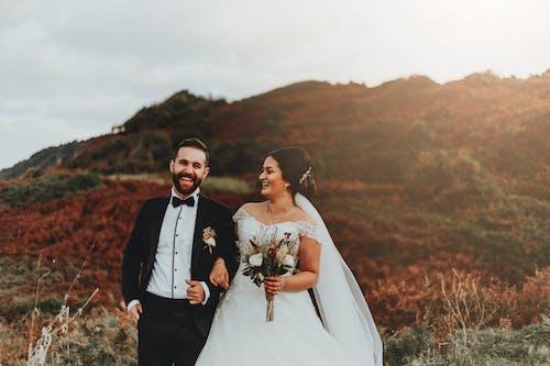 Cheerful newlywed couple walking in field