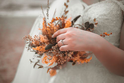 Bride in white dress touching wedding bouquet
