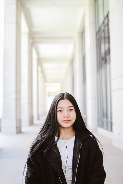 Charming young Asian woman with long black hair in white blouse and fur coat looking at camera with half smile while standing at spacious street next to row of big columns