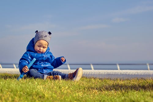 Cute Boy in a Blue Jacket Sitting on the Grass